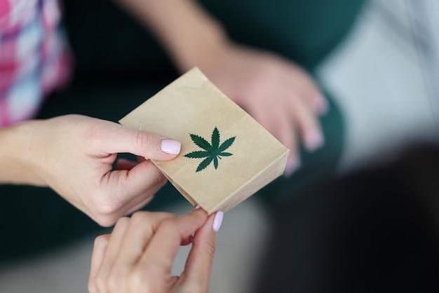 Main Féminine Tient Un Sac En Papier Avec Une Image Du Symbole De La Marijuana Photo Premium