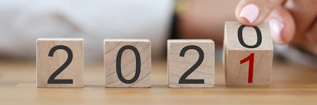La Main Féminine Transforme Le Numéro 2020 En Numéro 2021 Avec Son Doigt. Photo Premium