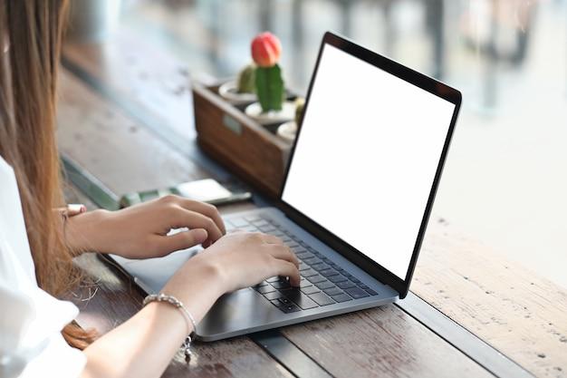 Main féminine travaillant avec son ordinateur portable sur une table en bois Photo Premium