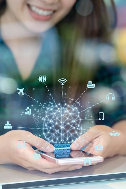 Main de femme d'affaires asiatique agrandi à l'aide du mobile avec cerveau polygonal Photo Premium
