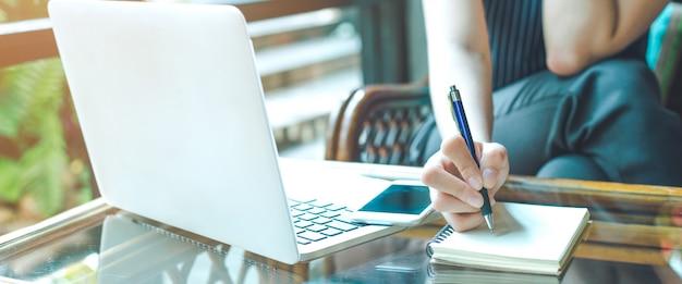 Main de femme d'affaires écrit sur un bloc-notes avec un stylo et à l'aide d'un ordinateur portable. Photo Premium