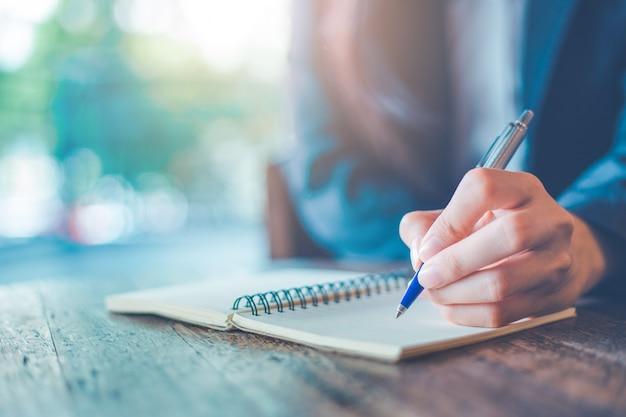 Main de femme d'affaires écrit sur un bloc-notes avec un stylo dans le bureau. Photo Premium