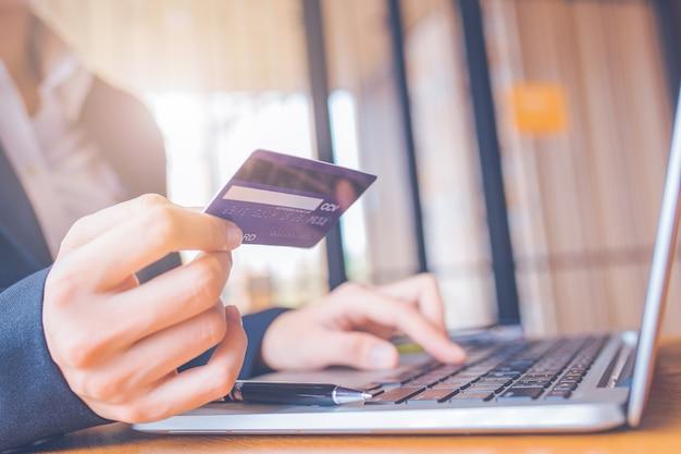 Main de femme d'affaires est titulaire d'une carte de crédit bleue. Photo Premium