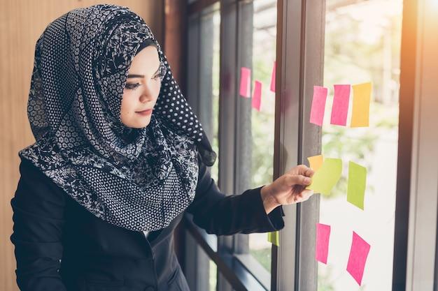 Main de femme d'affaires musulmanes asiatiques, ramasser des notes autocollantes sur le mur de verre. Photo Premium