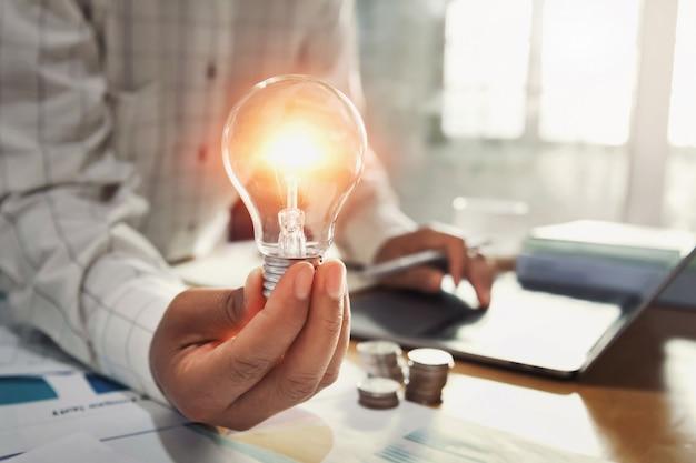 Main de femme d'affaires tenant l'ampoule avec pile de pièces sur le bureau. Photo Premium
