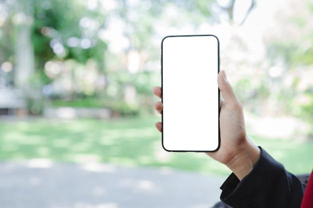Main de femme à l'aide d'une maquette de smartphone et d'un jardin vert flou Photo Premium