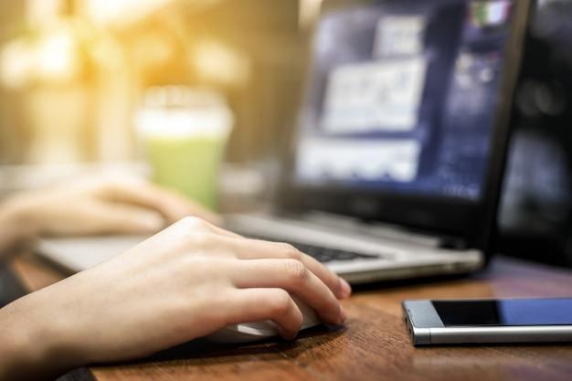 Main de femme à l'aide d'un ordinateur portable pour le travail travail en milieu de travail dans l'espace café de café Photo Premium