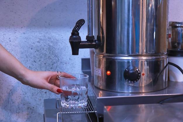 La Main D'une Femme Appuie Sur Le Robinet Pour Verser L'eau Chaude De La Chaudière Dans Un Verre Transparent Sur La Table Photo Premium