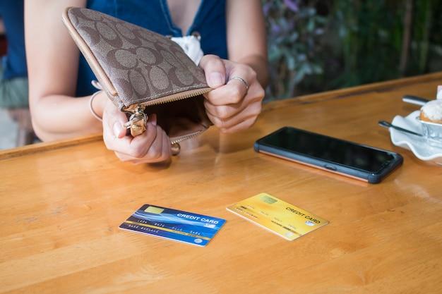 Main de femme asiatique pauvre ouvrir le sac à main vide à la recherche d'argent Photo Premium