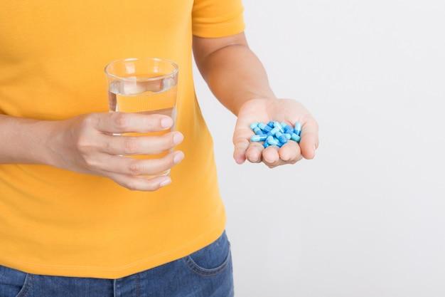 Main de femme asiatique tenant la capsule et le verre sur fond blanc Photo Premium