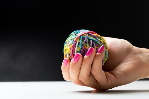 Main de femme avec balle d'élastiques colorés Photo Premium