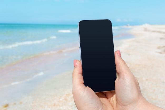 Main De Femme Belle à L'aide D'un Téléphone Intelligent à La Plage Photo Premium