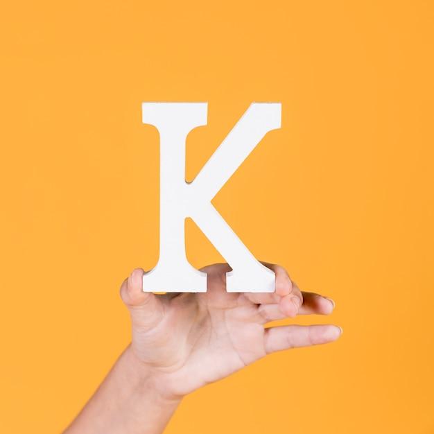 Main de femme brandissant l'alphabet de la capitale k Photo gratuit