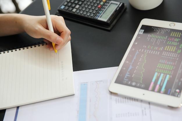 Main de femme de bureau travaillant sur le business papers et tablette Photo Premium