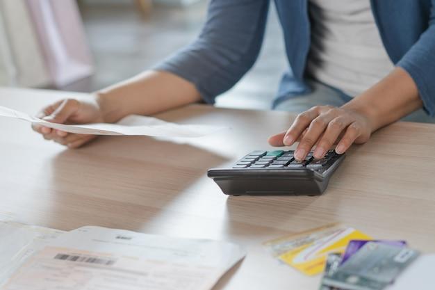 Main de femme calculant les dépenses mensuelles et la dette de carte de crédit. Photo Premium