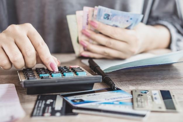 Main de femme calculant les dépenses mensuelles pour carte de crédit Photo Premium