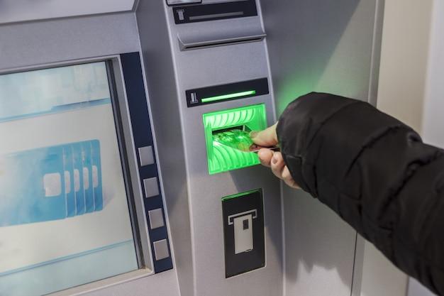 Main d'une femme avec une carte de crédit, utilisant un guichet automatique. femme utilisant un Photo Premium
