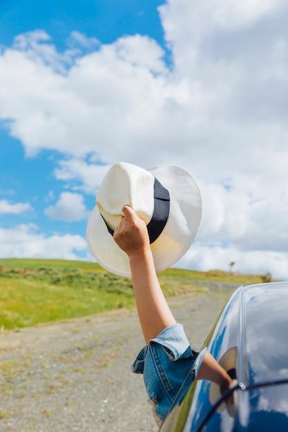 Main de femme avec chapeau contre ciel Photo gratuit