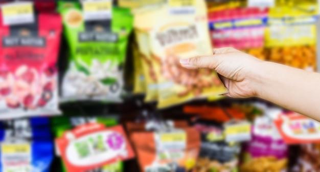 Main de femme choisissant ou prenant des produits sucrés, des collations sur les étagères dans un dépanneur Photo Premium