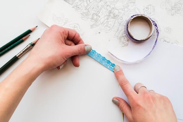 Main de femme collant la dentelle bleue sur papier à dessin sur le fond blanc Photo gratuit