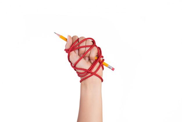 Main de femme avec un crayon jaune attaché avec une corde rouge, liberté du concept de la presse. Photo Premium