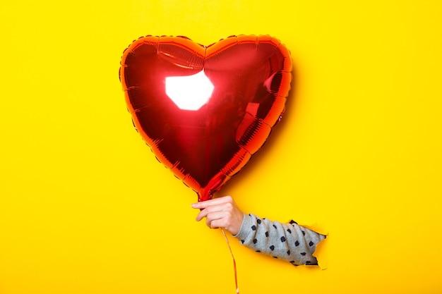Main De Femme Dans Un Fond Jaune Déchiré Tenant Un Coeur De Ballon Rouge Gonflable à Air. Photo Premium