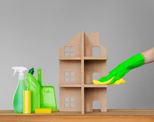 Une main de femme dans un gant de caoutchouc lave la maison symbolique avec un drap vert Photo Premium