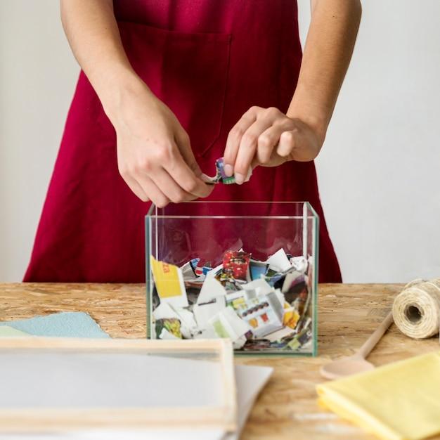 Main de femme déchire le papier sur un récipient en verre dans l'atelier Photo gratuit