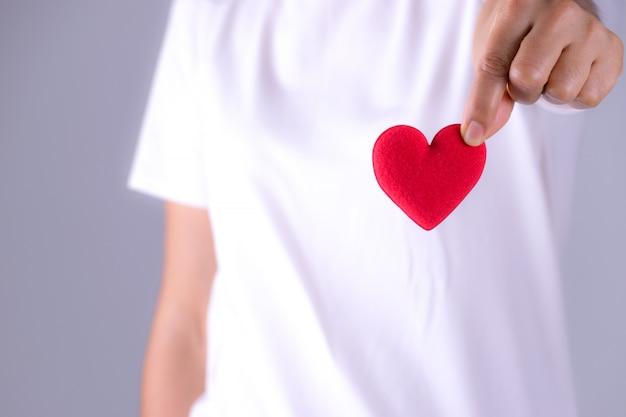 Main de femme donne un coeur rouge pour le concept de la journée mondiale du coeur Photo Premium