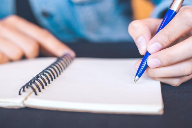 Main de femme écrit sur un bloc-notes avec un stylo dans le bureau. Photo Premium