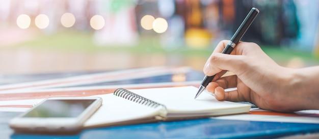 Main De Femme écrit Sur Un Bloc-notes Vierge Avec Un Stylo Sur Un Bureau En Bois.bannière Web. Photo Premium