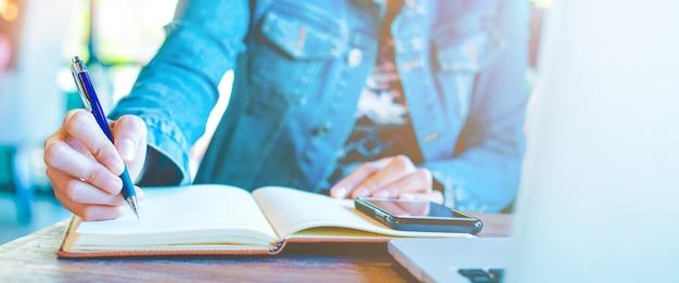 Main de femme écrivant sur le bloc-notes avec un stylo Photo Premium