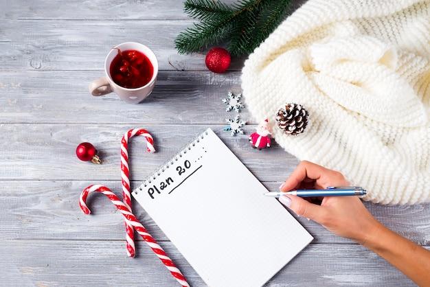 Main de femme écrivant des vœux de noël Photo Premium