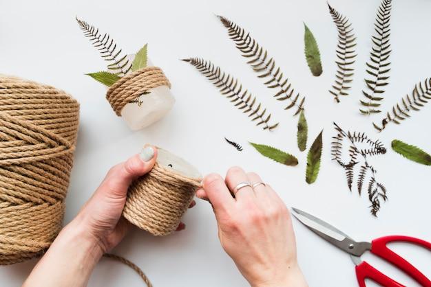 Main de femme enveloppant la ficelle sur la bougie avec des feuilles et des ciseaux sur fond blanc Photo gratuit