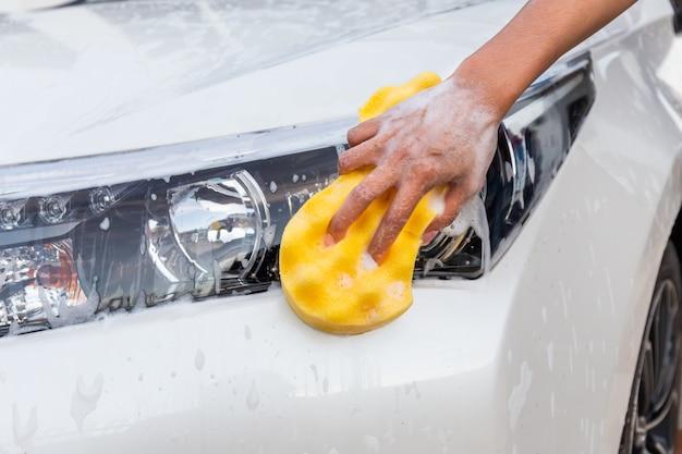 Main de femme avec une éponge jaune, lavage de phare de voiture moderne ou automobile de nettoyage. Photo Premium
