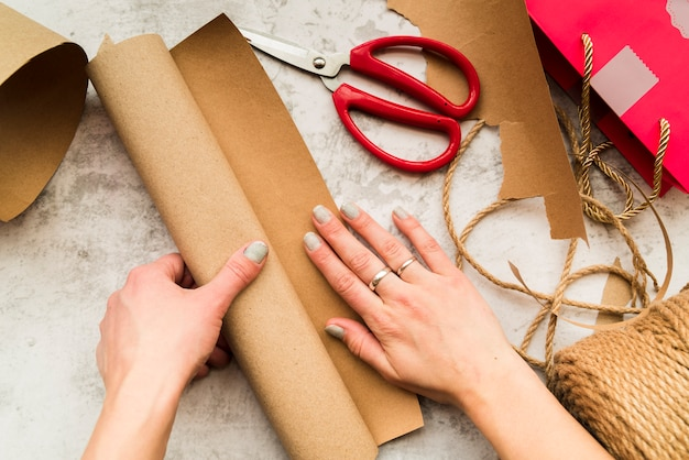 Main de femme faisant le métier avec du papier brun sur fond texturé Photo gratuit