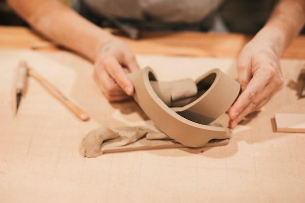 Main de femme faisant un produit créatif avec de la terre sur un bureau en bois Photo gratuit