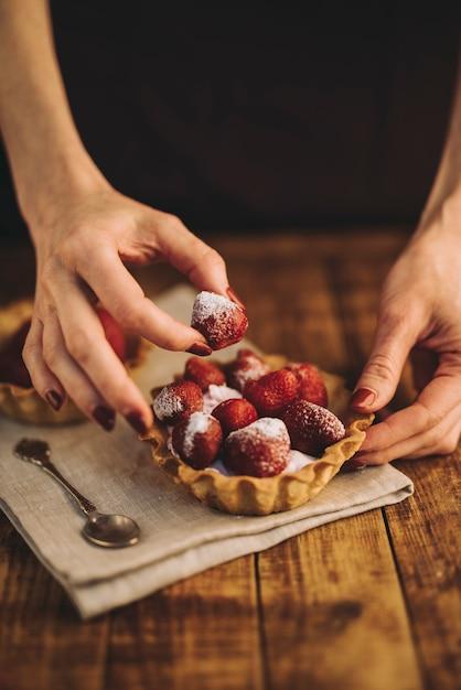 Main de femme faisant la tarte aux fraises sur une table en bois Photo gratuit