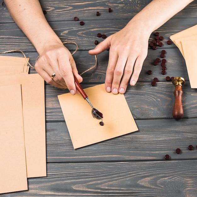 Main de femme gros plan verser cire fondue sur enveloppe sur fond de texture en bois Photo gratuit