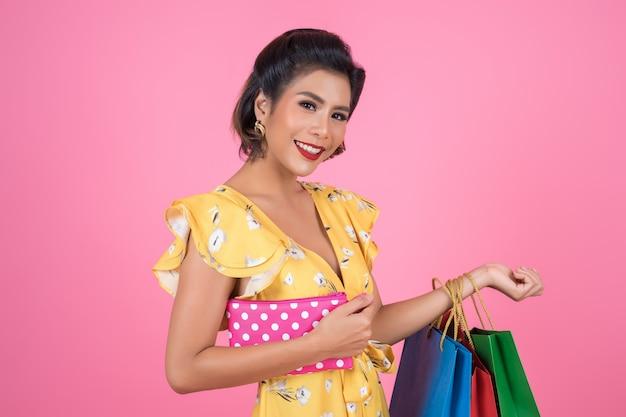 Main de femme jeune fashion holding portefeuille et sacs à provisions Photo gratuit