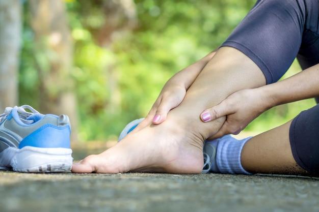 Main de femme massant sa jambe tordue à la cheville cassée Photo Premium