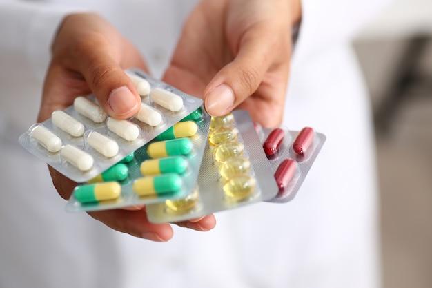Main de femme médecin tenant pack de différents Photo Premium
