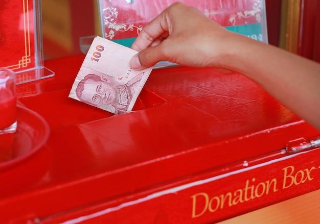 Main de femme mettant de l'argent pour l'offroire dans une boîte de dons Photo Premium