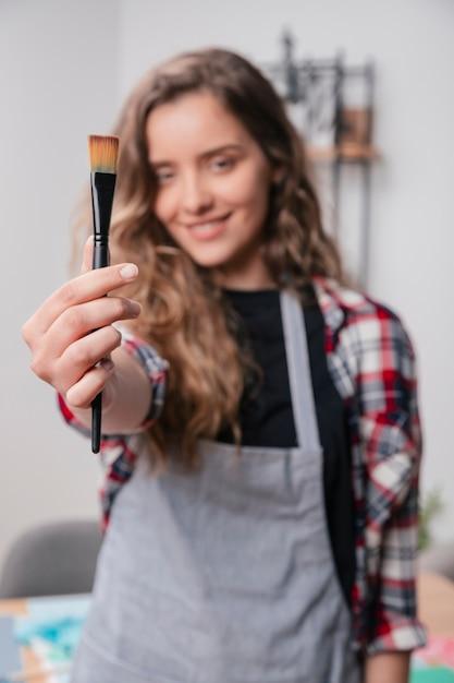 Main de femme montrant un pinceau inutilisé noir Photo gratuit