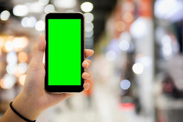 Main de femme montre un smartphone mobile avec écran vert en position verticale Photo Premium