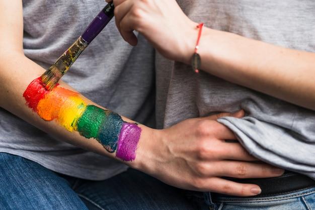 Main de femme peignant le drapeau arc-en-ciel sur la main de la petite amie avec un pinceau Photo gratuit