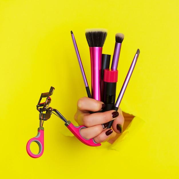 Main de femme avec pinceaux, mascara, rouge à lèvres, recourbe-cils pour maquillage Photo Premium