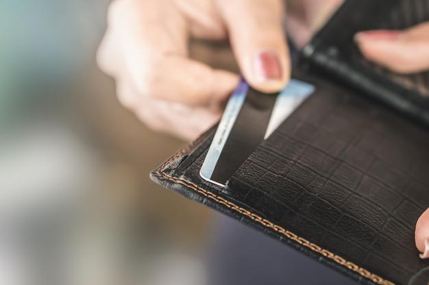 Main de femme prenant la carte de crédit du sac à main noir Photo Premium