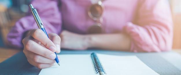 Main De Femme Prenant Des Notes Sur Un Ordinateur Portable à L'aide D'un Stylo. Photo Premium