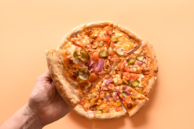 La Main De La Femme Prend Une Pizza Italienne Fraîche Avec Des Légumes. Photo Premium